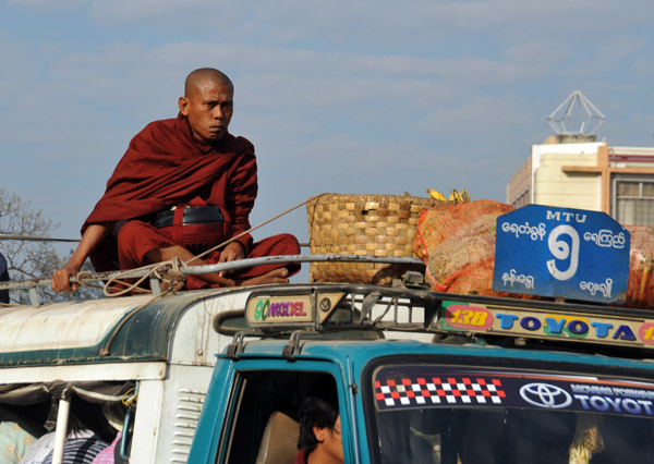 Monk riding on the roof of a packed MTU local bus, Mandalay