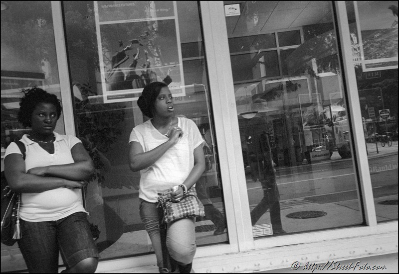 Two young women looking at man on Biscayne Boulevard in Downtown Miami, Florida, USA, 2011. Street Photography of Miami, San Francisco and Key West by Emir Shabashvili, see http://street-foto.com, http://miamistreetphoto.com, http://miamistreetphotography.com or http://miamistreetphotographer.com