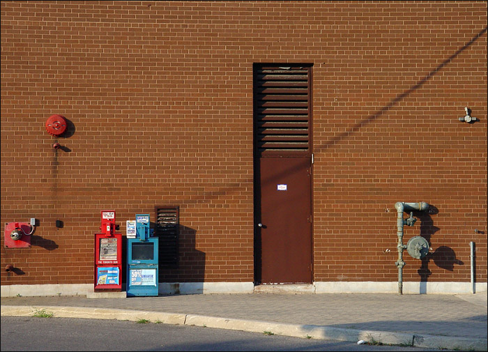Newspaper boxes, industrial miscellany, and shadows