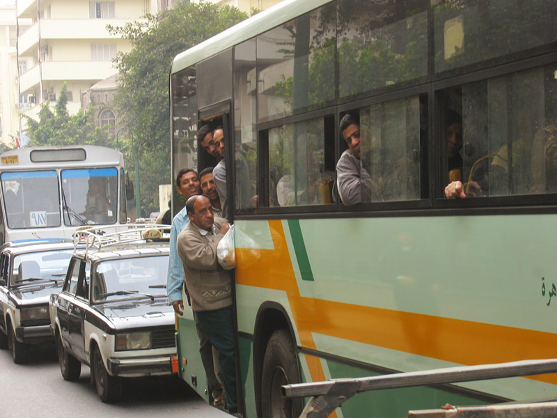 An overfilled bus in the usual heavy traffic.