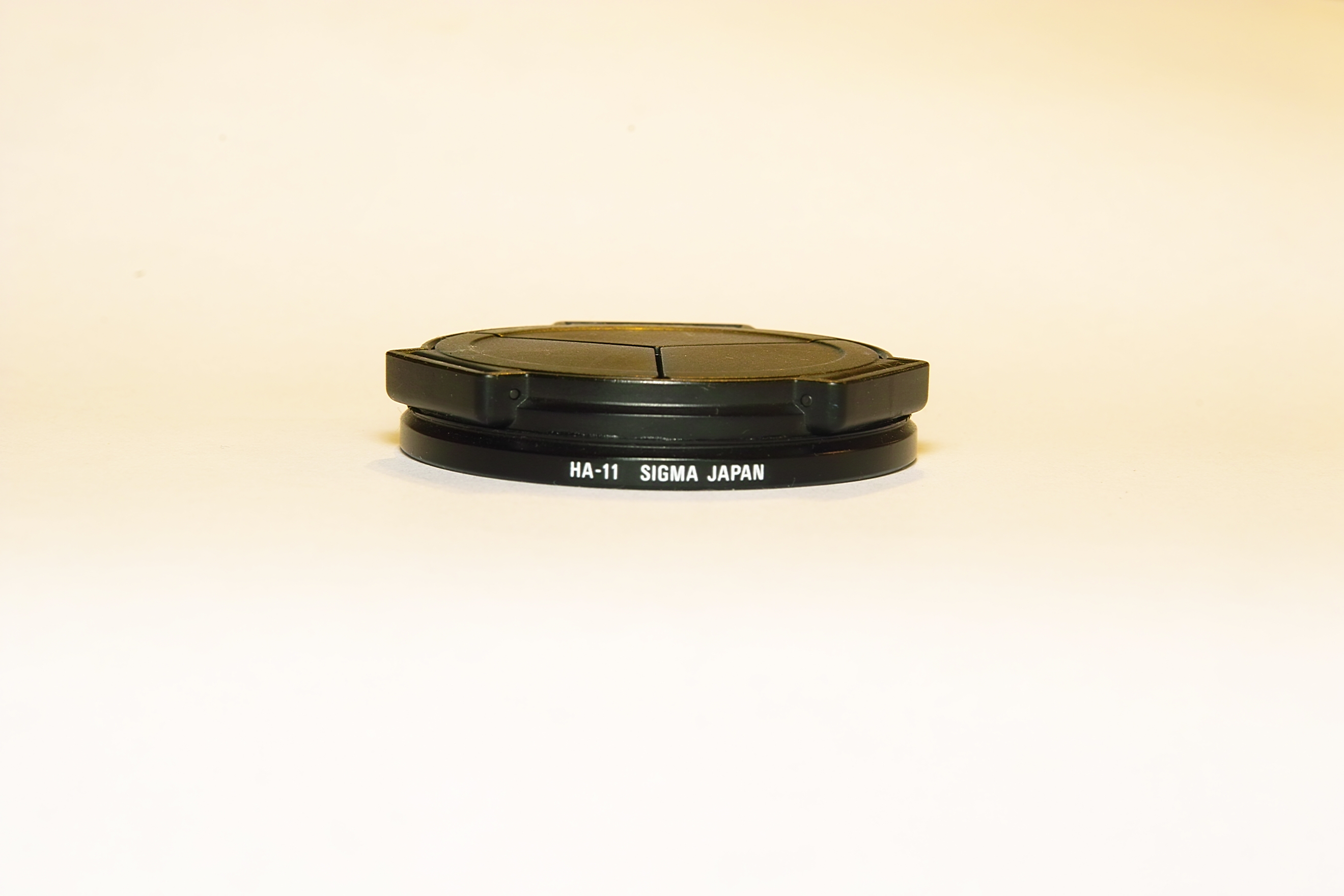 Ricoh LC-1 Auto Lens Cap attached to Sigmas HA-11 ring.