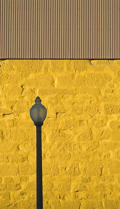 Lone lamp against yellow wall