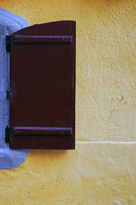 The brown window, the yellow wall and a little of blue