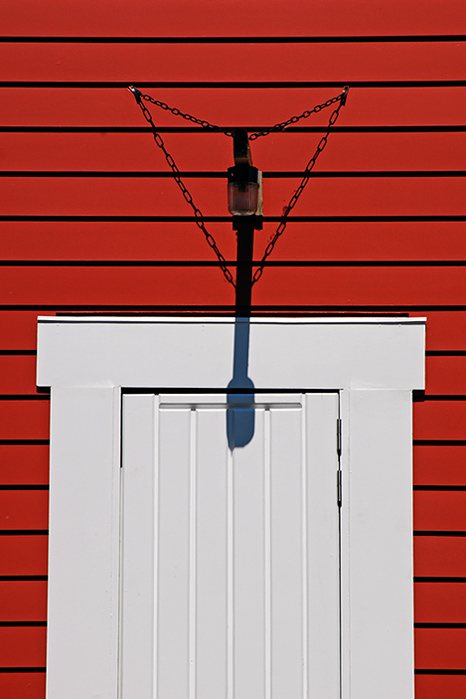 White door, red wall and lamp shadow