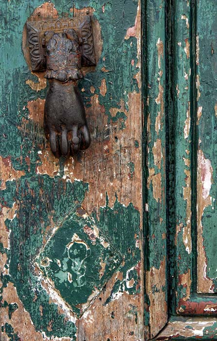 The green door with the hand and ring