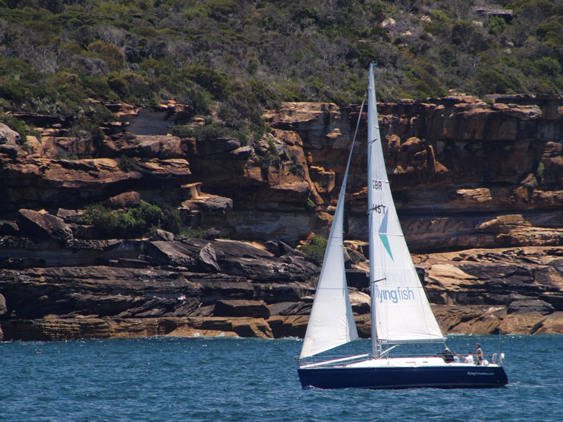 Small yacht, geology in background
