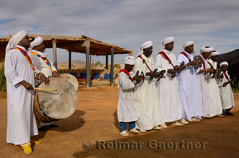 Group of Gnawa musicians in white robes dancing and playing krakeb and drum in Khemliya Morocco
