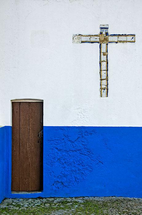 Blue wall, brown door, cross in white
