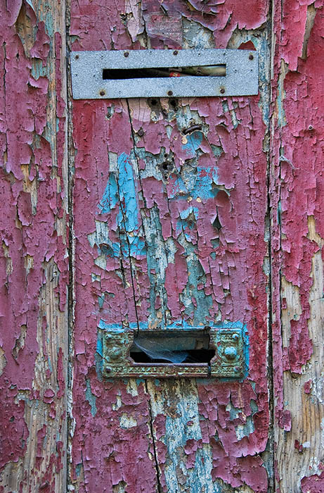 The mail slots in the old red wooden door