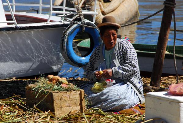 Uros woman peeling vegetables