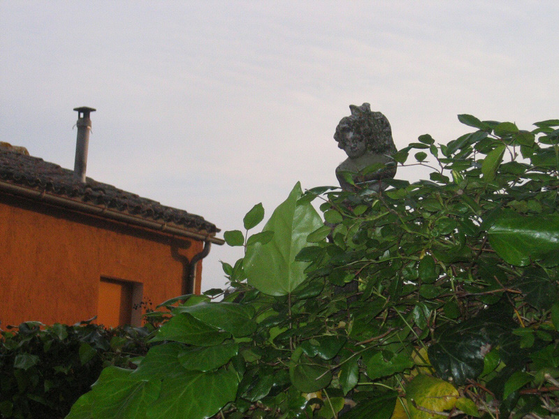 Garden statue, a little after 7pm.  Cat on her back?