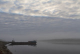Barge in fog, cloudy sky above