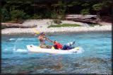Piero paddles Liz down the stream to reach the camp.