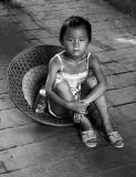 A hot a humid day for a small girl. She found relief by sitting in a hat in the shade.