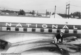 Early 1950's - a fueler servicing the oil on a National DC-6B