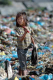 Young girl uses a tool for picking through the trash.