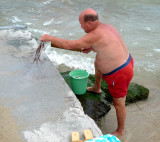This fisherman is slamming the octopus  on the rock to make it soft ...  Then eat raw