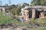 Slum dwellings with sewage draining into the stream in the foreground and high rises in the background