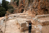Banias: Judy on the ruins of the Goat Temple. Behind her: Nemesis Courtyard, Temples of Zeus & Pan, and the cave.