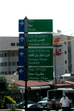 Street sign in Nazareth indicating how to get to different cities, towns and roads. Sign is in Hebrew, Arabic and English