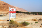 Sign in Hebrew, English and Arabic - swimming prohibited  in the Dead Sea there. A grove is in this desert area - an oasis.