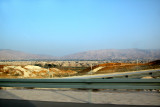 Driving through the West Bank: Fence separates Jordan from the West Bank. Jordanian village & mountains are in background.
