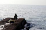 A fisherman on a jetty - the beach in Tel Aviv on the Mediterranean Sea.