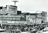 Nathan's at Coney Island - famous for its hot dogs. The Parachute Jump  & the Wonder Wheel rides are in the background. (1950's)
