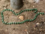 Left Green Beads by a Cherry Tree Trunk