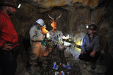 Tour guide explaining how the miners make offerings of coca leaves and alcohol to El Tio.