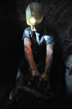 A drunk miner dragging his air hammer out of the mine after a long day's work.