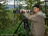 HIGHLAND BIRDING. I'm waiting for montane birds at elevation 2155 meters (Bauko, Mountain Province) when my brother Jeff snapped this pic.  My light birding combo is the 20D + 500 f4 L IS + Canon 1.4x TC, mounted on a Manfrotto 3421 gimbal head and 475B tripod. The black bonnet insulates my top spot against the cold mountain temperature, as my hair had divorced me about a decade ago....;-)  [350D + Sigma 10-20, hand held]