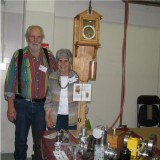(101)   Carl and Carole Felty in front of their clock.