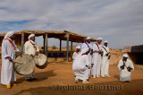 Group of Gnawa musicians in white robes dancing to krakeb and drum in Khemliya Morocco