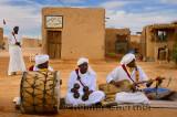Gnawa music group in white turbans and jellabas sitting and playing music in Khemliya desert village Morocco