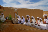 Group of Gnawa musicians in white turbans and jellabas sitting and playing music in Khemliya Morocco