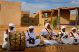 Khemliya Gnawa musicians in white turbans and jellabas playing while sitting in a desert village Morocco