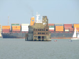 A container ship passing between the two forts.