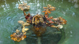 Elaborate metal sculpture in the fountain with a violinist and flower petals.