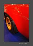 Golden rim of a red Lamborghini on a blue carpet