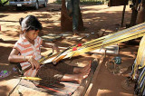 A small Kreung orphan, weaving to support her grandmother in Krase, Cambodia.