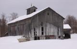 worn wood barn in snow