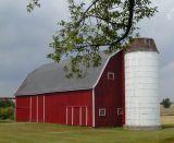 dark red barn with bright white silo...