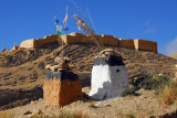 A pair of shrines with prayer flags roadside at the base of the fort
