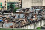 Tin shanties behind a high wall, Recto Avenue, Manila