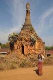 Old woman passing a ruined stupa, Nyaung Ohak