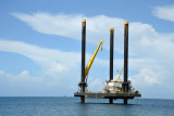 Reflecting Angola's new source of wealth, an oil platform sitting off the end of Ilha do Cabo