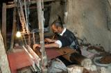 Weaver at work on a loom making a rough heavy cloth