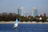 Twin towers of the Bank of Tanzania behind the seafront of Ocean Road, Dar es Salaam with an outrigger sailboat