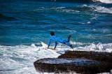Surfer jumping from rocks at Avalon